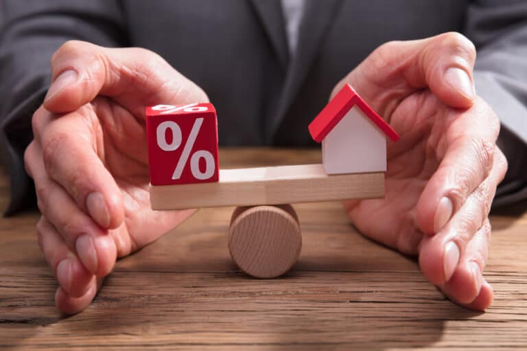 Close-up of hands balancing a little house and percentage sign