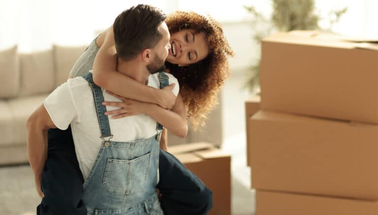 Smiling young couple embracing in front of cardboard packing boxes