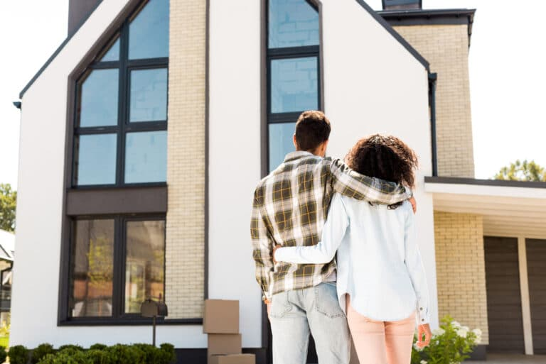 Young couple from behind with their arms around each other, looking at beautiful house