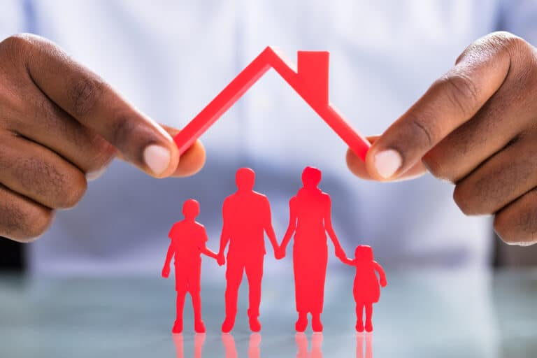 Close-up of man's hands holding red cut-out of roof over red cut-out of family